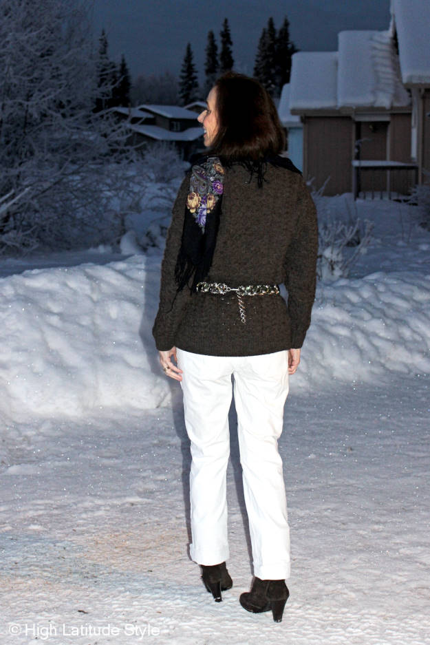 fashion blogger over 50 donning a casual winter look with white jeans and a cableknit sweater and Russian floral print wool scarf