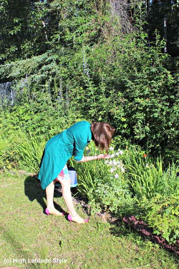 #midlifestyle woman over 40 wearing a dress and picking flowers