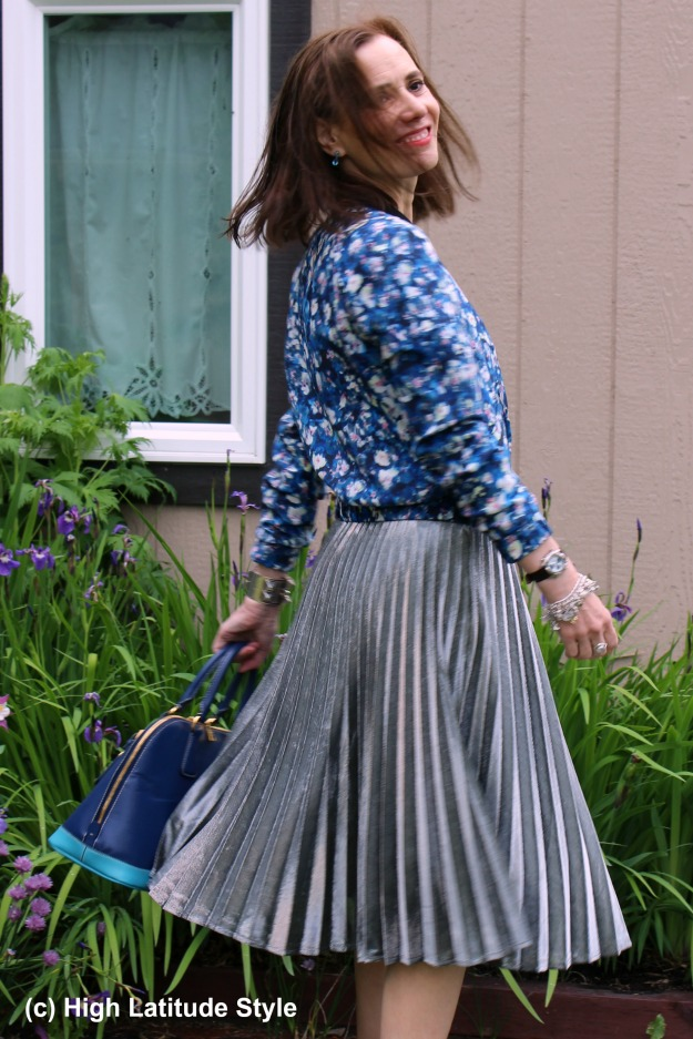 #fashionover40 mature woman donning trendy silver pleated skirt with floral bomber