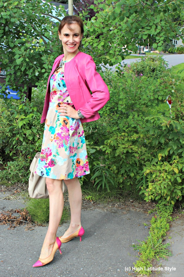 #fashionover50 Mature woman wearing a pink leather jacket and a floral print dress