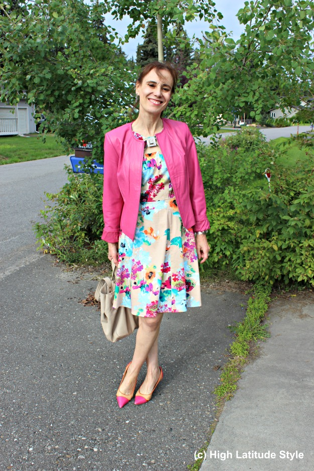 fashion influencer in pink leather jacket and printed dress with pink and yellow