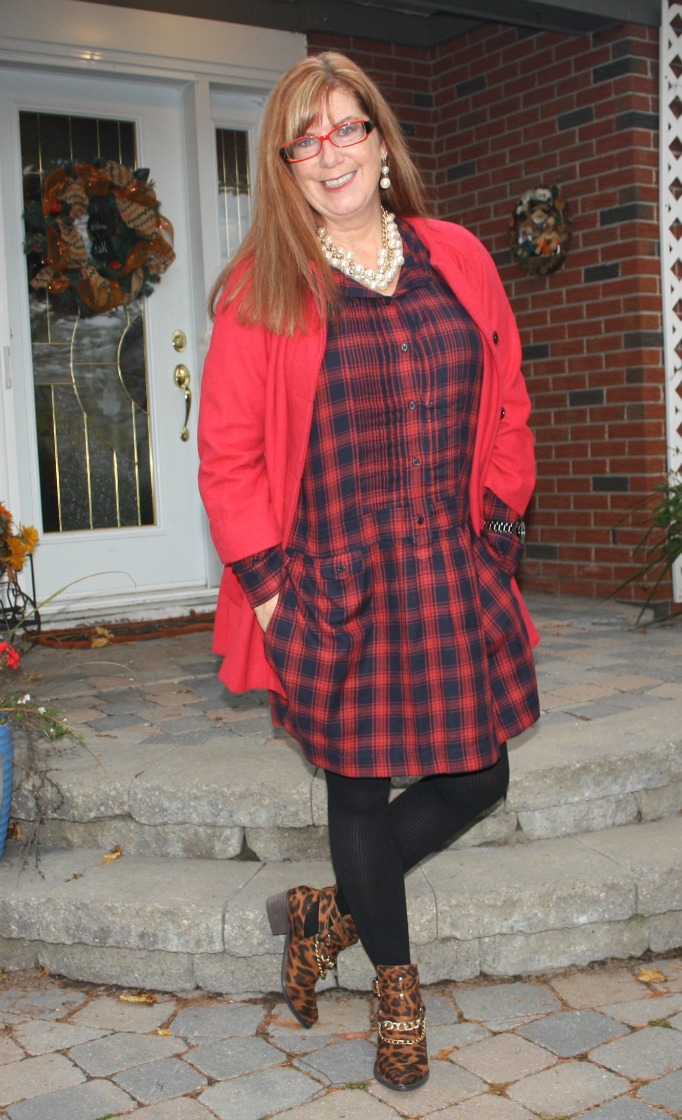 redhead wearing a red cardigan and red blue plaid dress with leopard prind booties