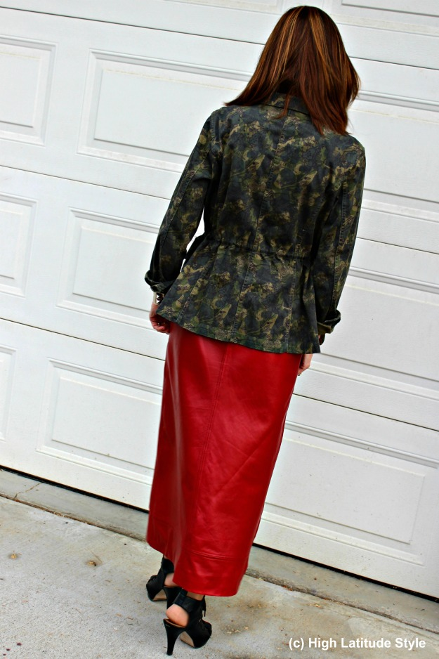 fashion blogger over 50 in camouflage jacket with red leather skirt