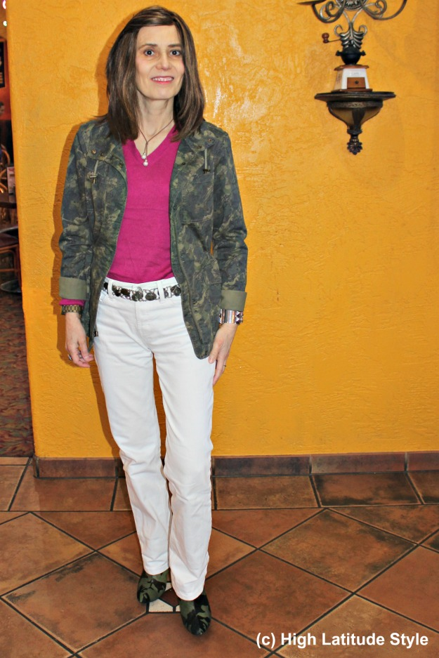 woman in camouflage utility jacket with white pants