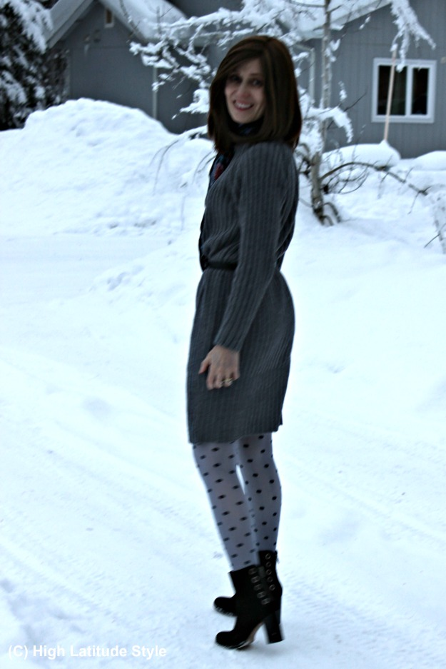 style blogger in monochromatic look with long knit dress, polka dot tights, belt and statement ankle boots