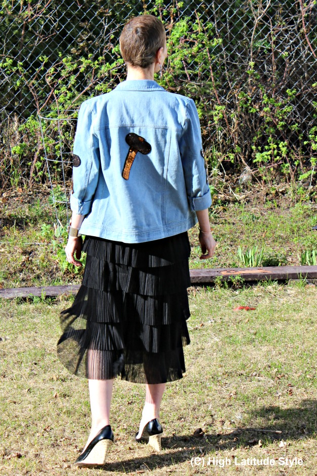 Nicole of the fashion over 50 blog High Latitude Style donning a pleated tired midi skirt with patched denim jacket