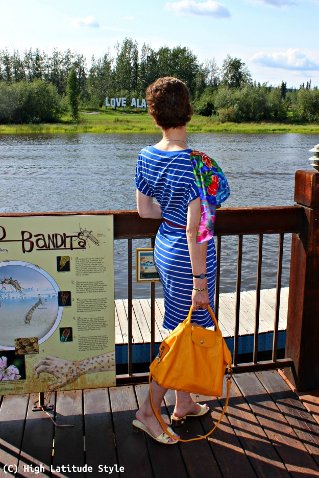 advanced style Nicole of High Latitude Style donning a posh casual T-shirt dress with scarf by the river