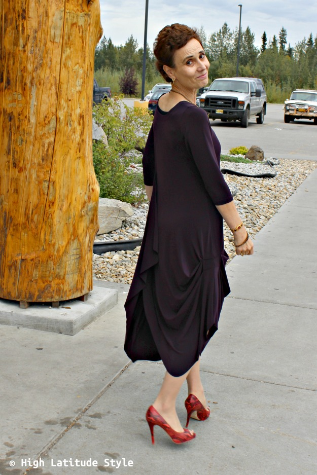 fashion blogger over 50 in a dramatic garment in aubergine