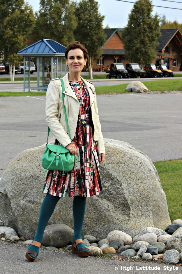 #fashionover50 woman looking posh in a green saddlebag and colorful dress and white motorcycle jacket
