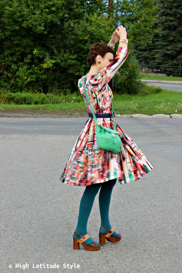 #fashionover50 mature woman in print dress with green crossbody
