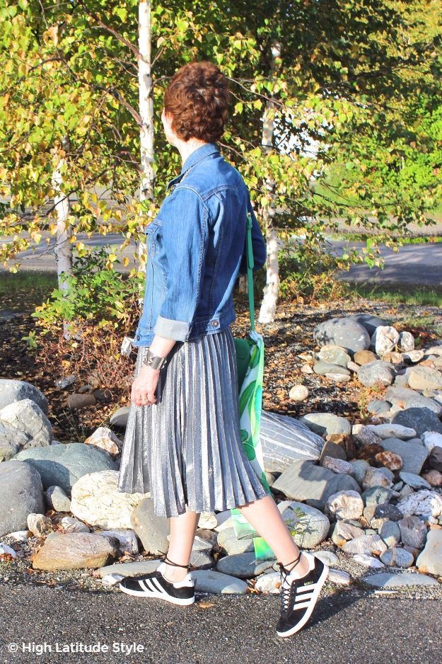 #over50fashion High Latitude Style showing how to wear a pleated skirt in fall with denim jacket and sneakers