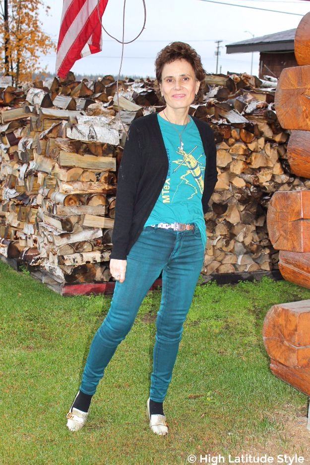 midlife woman in casual jeans, Tee, statement belt in front of firewood