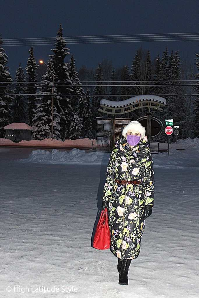 lifestyle blogger walking in boots over snow in the dark in a floral coat with hat and gloves purple mask