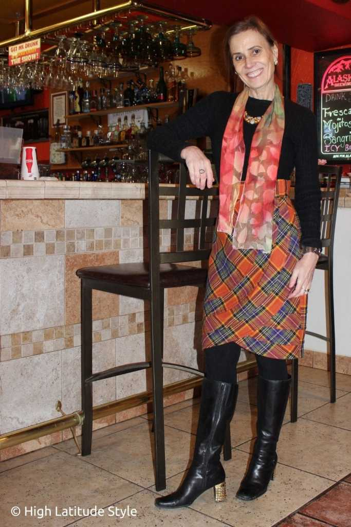 fashion influencer in orange plaid skirt and scarf, tall boots, tights cable knit sweater