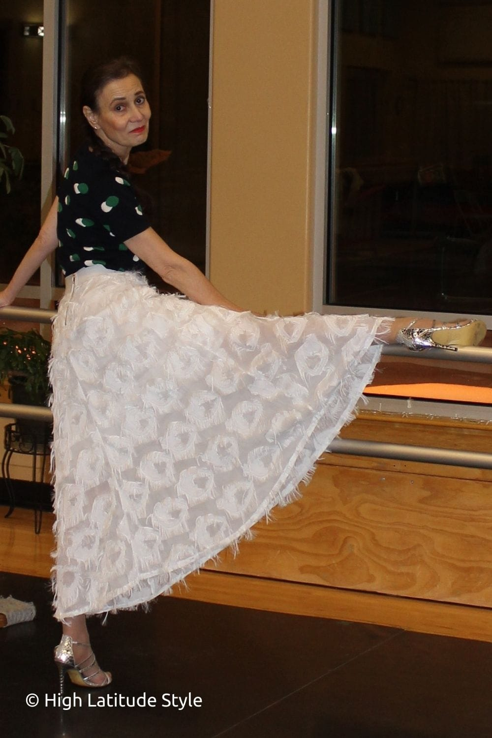 dancer stretching on bar in white skirt, polkadot top, silver dance shoes