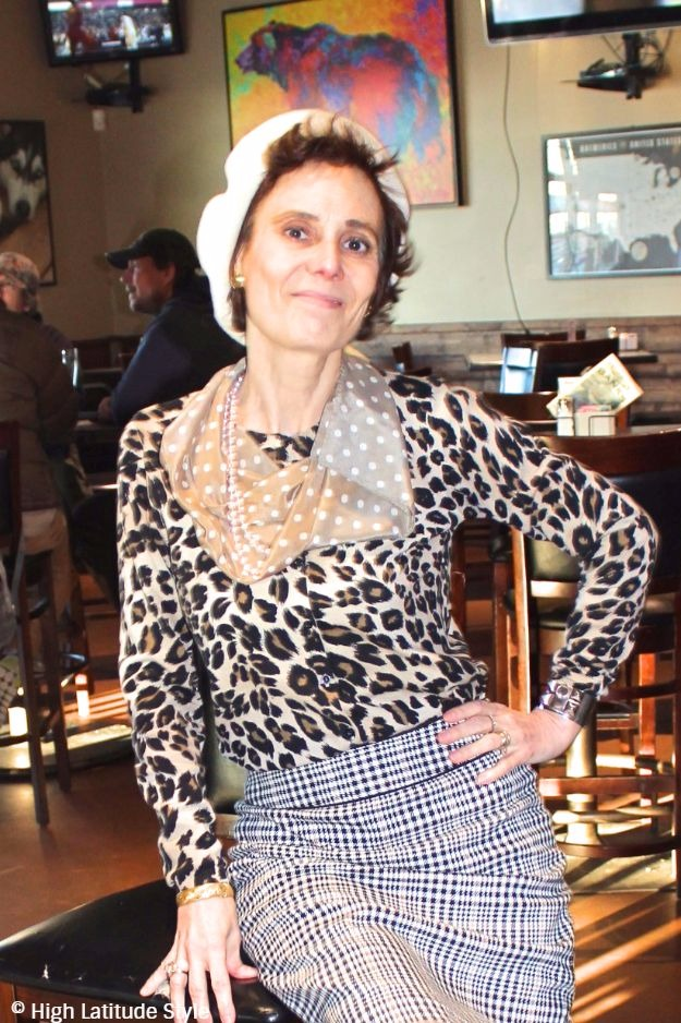 midlife woman sitting in a bar with beret and mixed pattern look