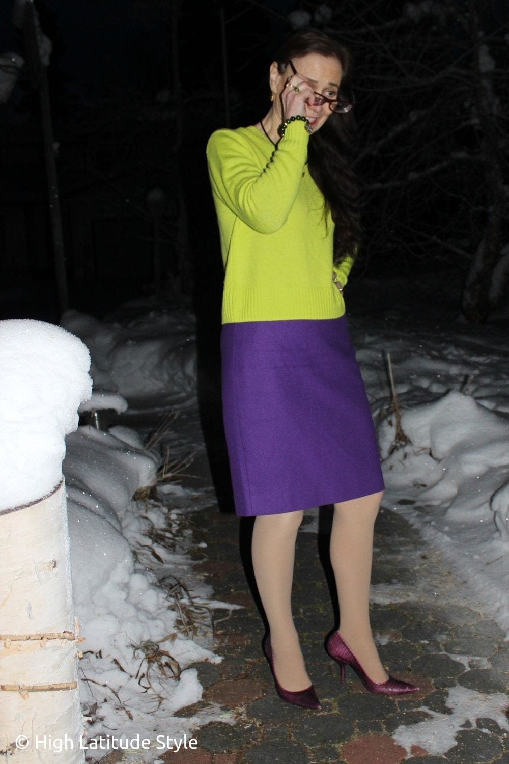 influencer in lemon top purple skirt flesh tights and matching heels