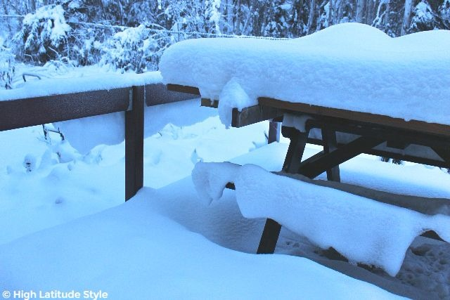 #AlaskaLife snow blankets hanging on the railing and bench of a deck in Interior Alaska