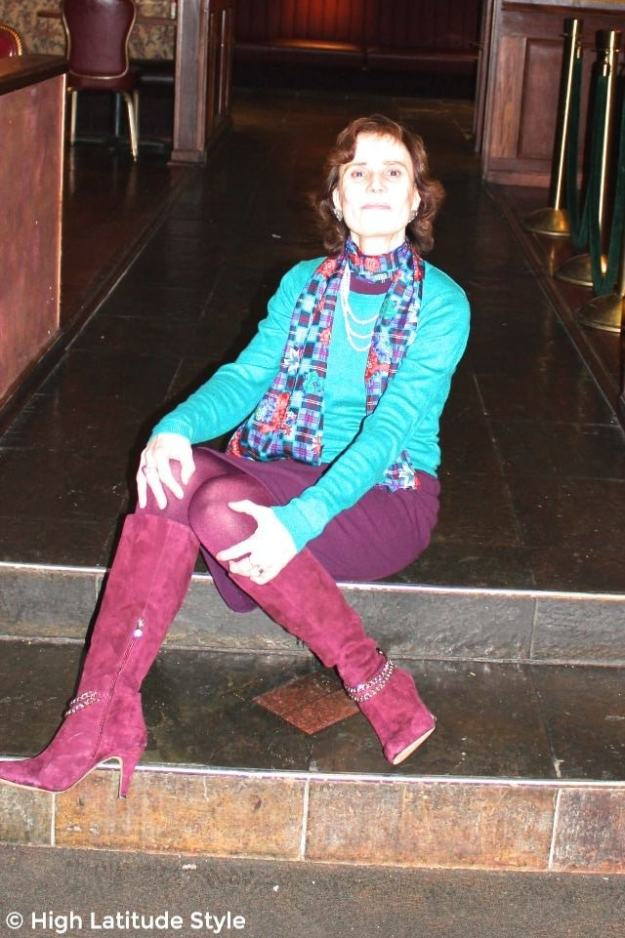 fashion blogger sitting on stairs in an outfit with teal sweater, burgundy sheath dress, tight and boots