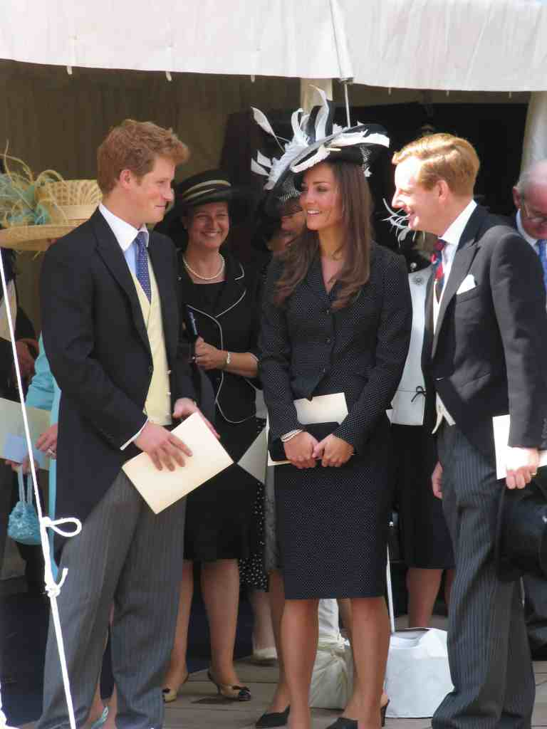 Kate Middleton in black skirt suit with white clutch, black and white hat