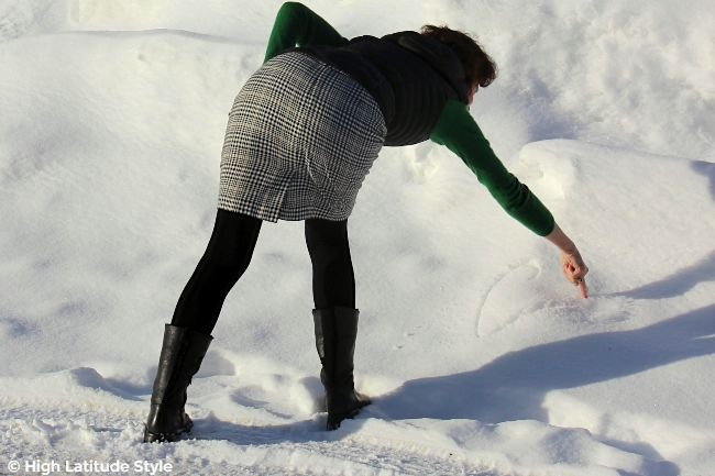 Alaskan woman drawing in the snow in plaid skirt meadow color sweater