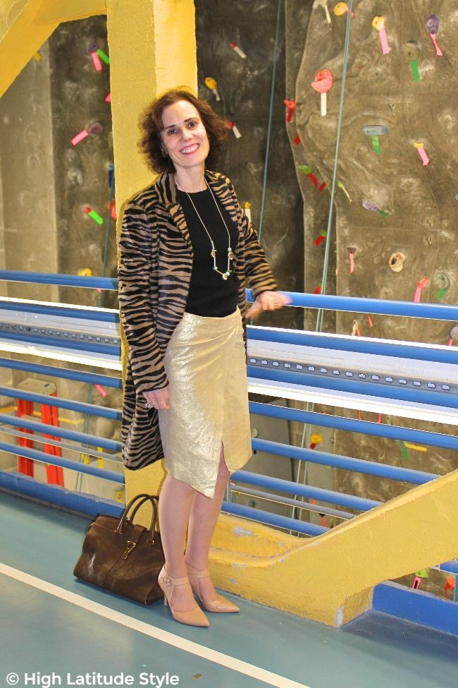 health and beauty blogger looking posh in a coat, gold color skirt and knit top
