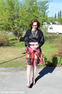#advancedstyle mature woman in summer office outfit with floral box pleat skirt, black long sleeve shirt, glasses, cardigan and pumps