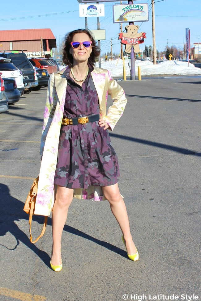 advancedstyle mature woman in purple gray dress with light yellow pink coat, sunflower yellow bag and neon yellow pumps