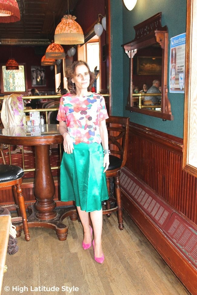 stylist in cheap multi-color top, teal skirt and great deal pumps