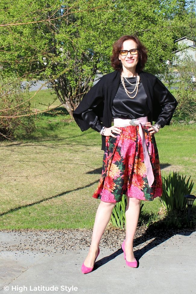#fashionover50 woman looking great in edgy oblong glasses, floral skirt, black top and pink pumps