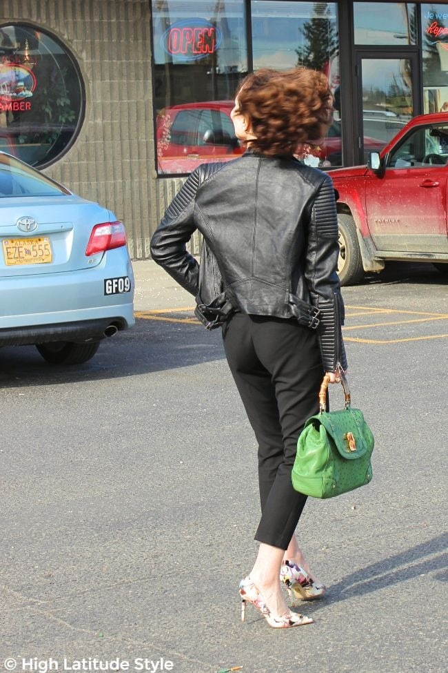 mature lady in black leather coat, cropped black trousers, colorful heels and green purse