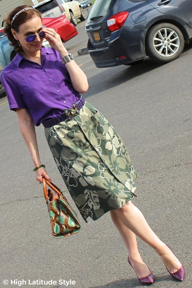 #fashionover50 mature woman in floral skirt, violet shirt, sunnies, structured bag, pumps, belt and head band