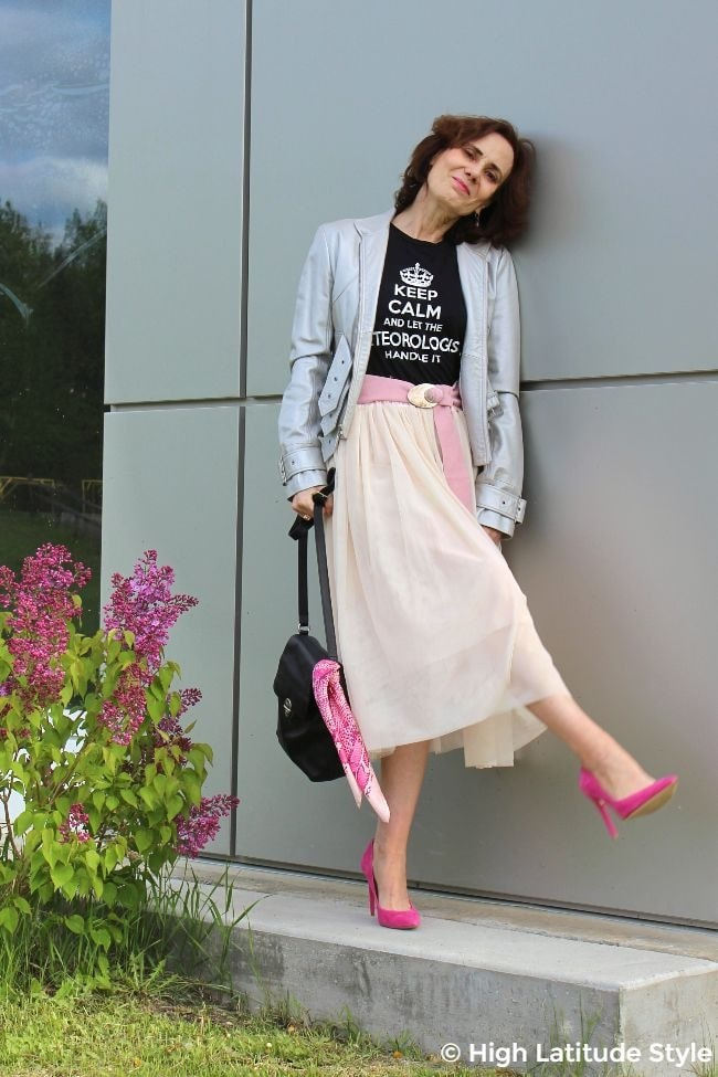 #streetstyleover50 midlife woman in street chic layered mesh skirt, pink heels, black graphic tee, and silver frock