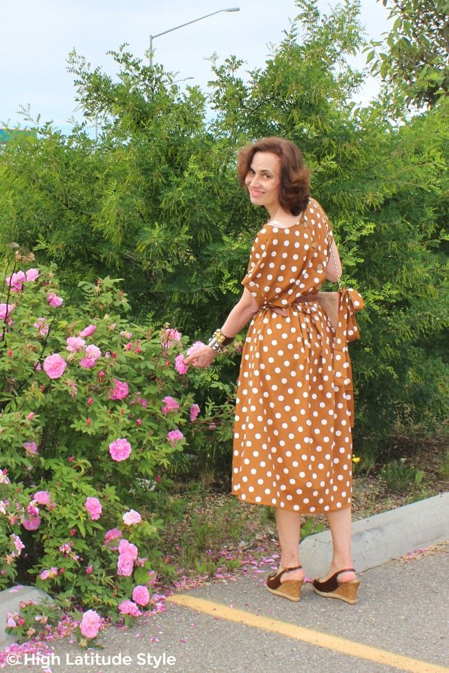 #fashionover50 midlife woman standing in front of a Sitka rose bush in a midi garment