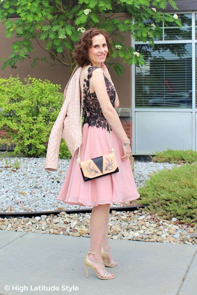 #advancedstyle midlife woman in fit-and-flare cocktail dress with cross body evening bag