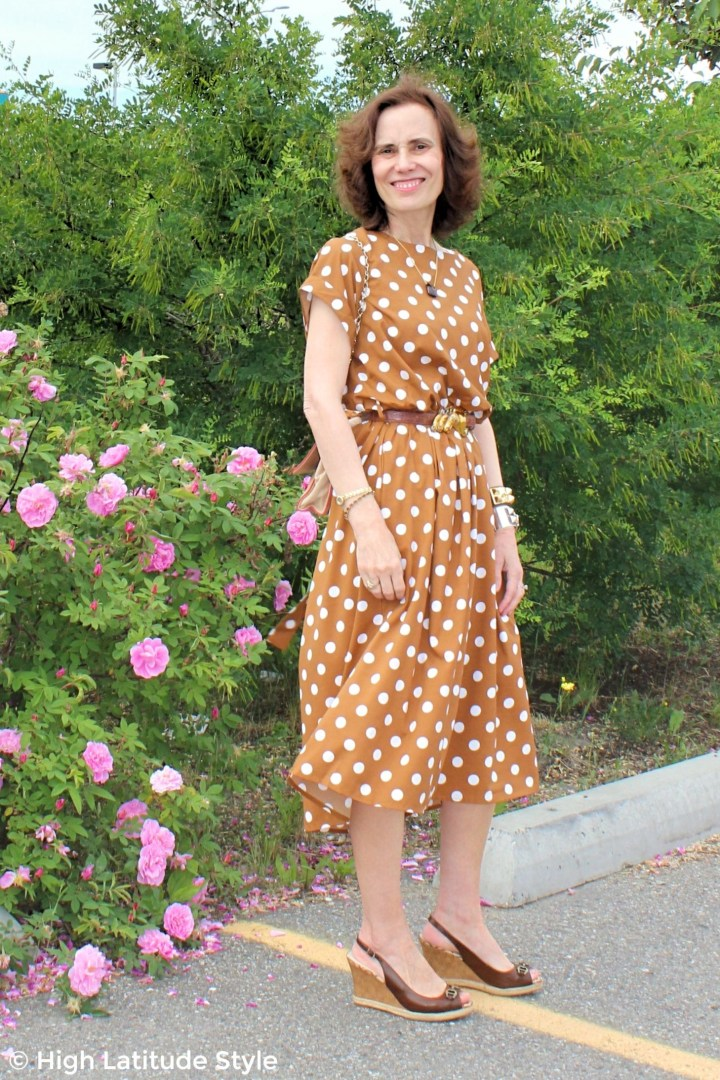 #advancedstyle midlife woman in summer outfit with polka dots in front of Sitka roses