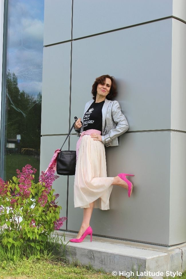 #fashionover50 mature lady in blush mesh skirt, pink shoes and belt, graphic tee and silver biker jacket posing at a silver wall