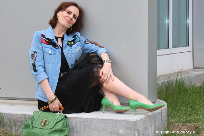 midlife woman sitting on a curb wearing a street wear outfit