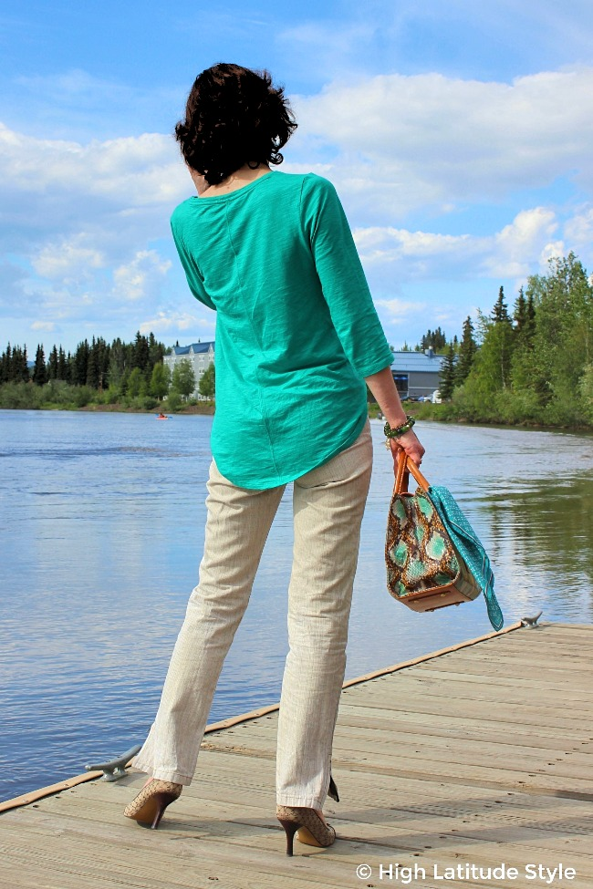 #advancedstyle lady looking onto the water in a teal and brown sightseeing top and pants combo