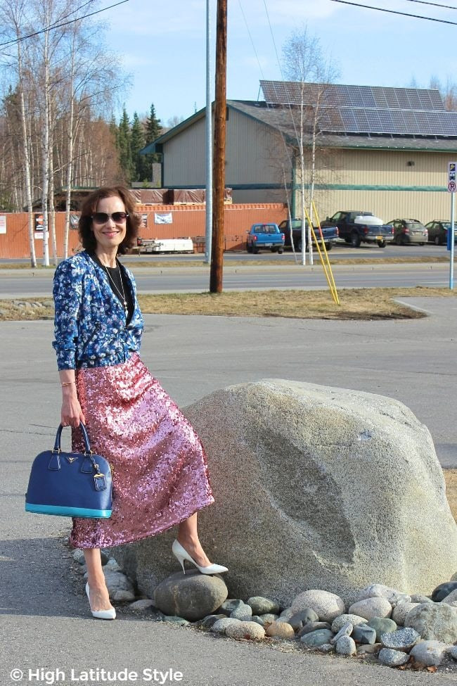 #fashionover50 woman in pink sequin midi skirt, two blue tones bag, white pumps, black top and blue pink white floral jacket