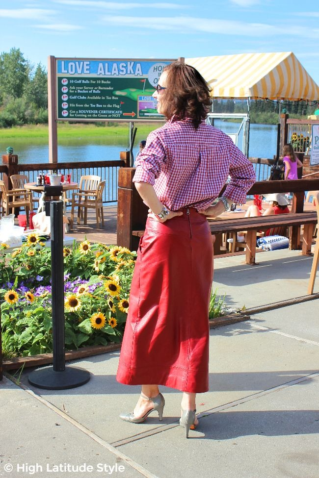 #styleover50 lady standing on a deck in a Tennessee diagonal placket red gingham blouse c/o #WhistleRiver and maxi leather skirt