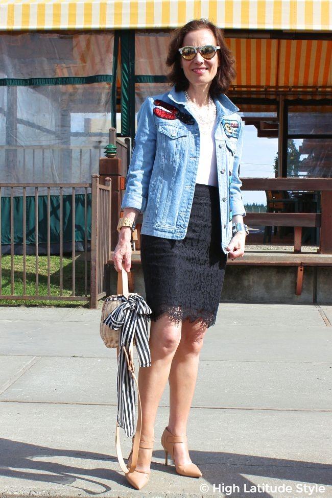 midlife woman in oversize sequin embellished denim jacket, lace skirt, pumps, and basket bag
