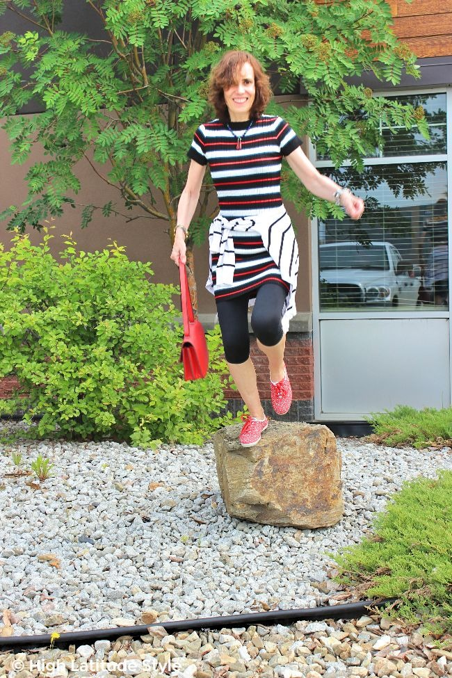 #advancedstyle older woman jumping of a stone in a sweater dress with leggings, crossbody bag