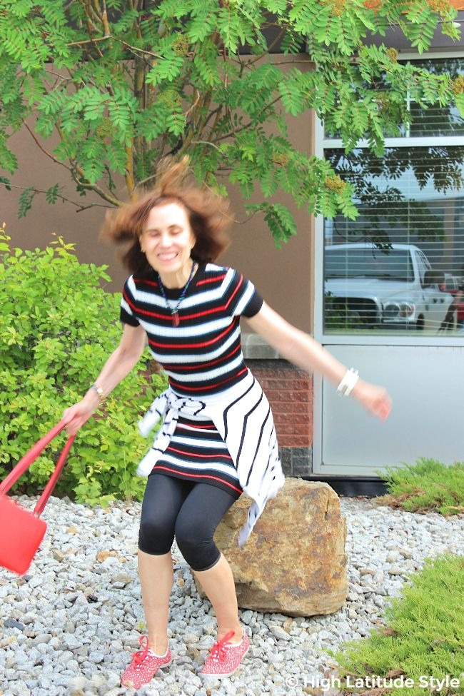 lifestyle blogger landing after jumping off a huge stone in a knit dress with purse and Keds