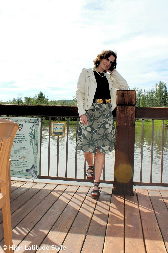 midlife woman in A-line DIY skirt, statement belt, motorcycle jacket, top and wood sandals