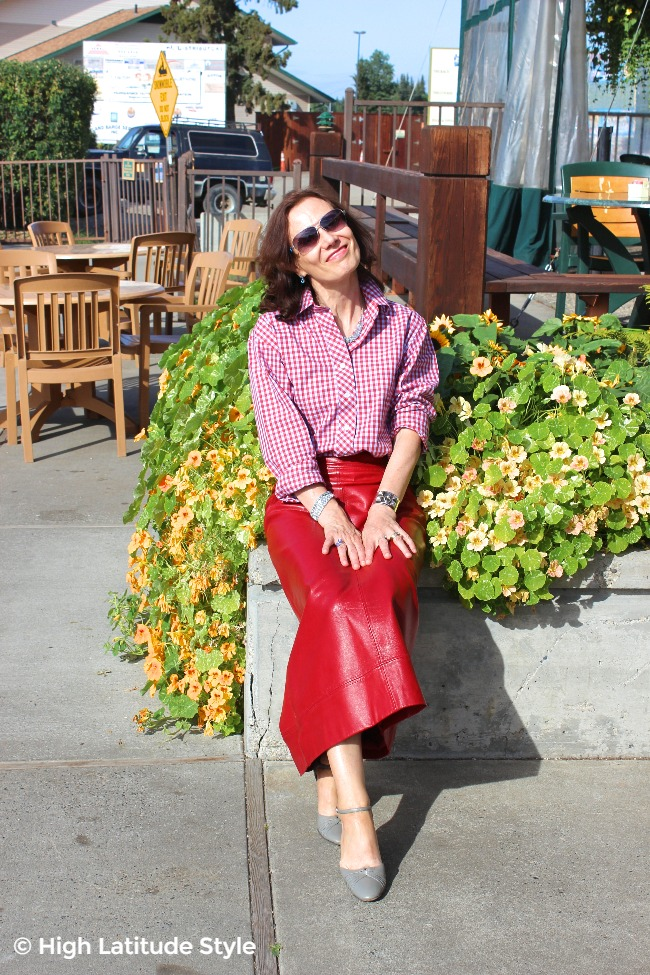 #advancedstyle older woman sitting on a deck wearing a red skirt and gingham blouse
