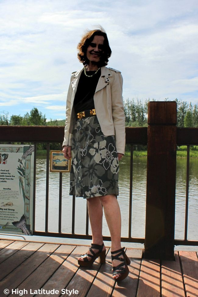 #styleover50 midlife lady in casual work outfit with floral bottom, black top, white biker jacket