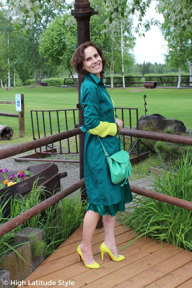 #advancedstyle woman in summer look with dress worn as coat over a skirt and blouse with matching purse and shoes