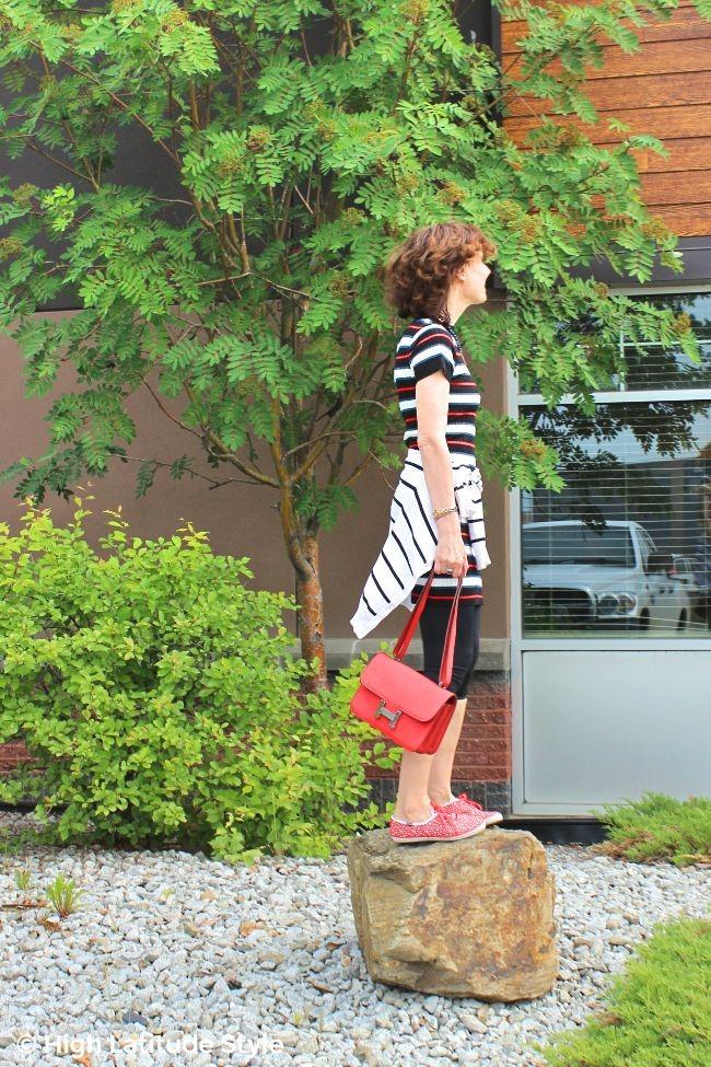 midlife blogger in striped mini dress, leggings, shoulder bag, polka dots canvas and H-bag