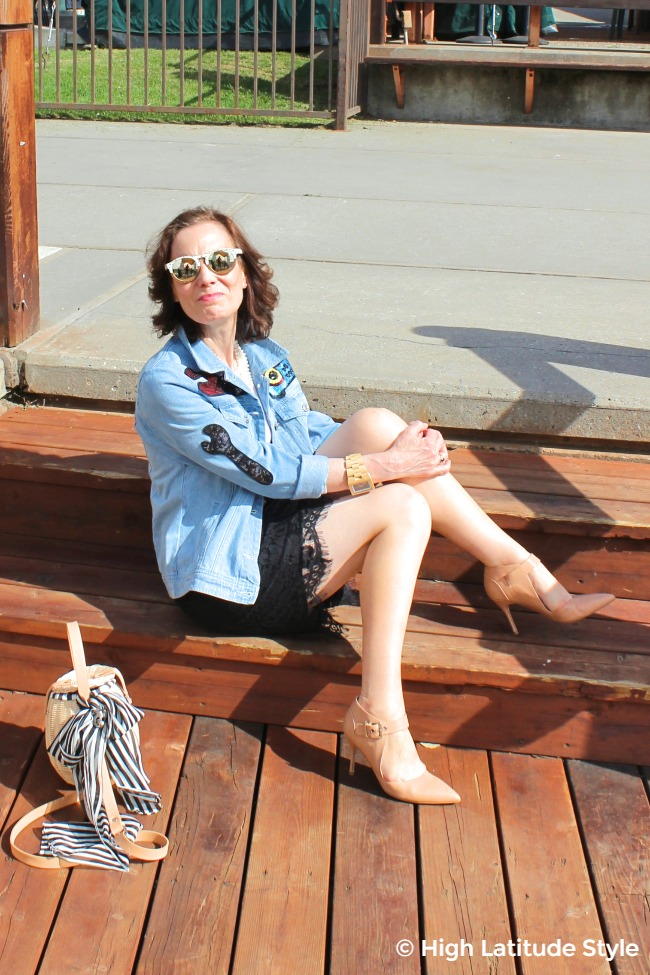 over 50 years old fashion blogger sitting on stairs in skirt, coat, pumps and sunglasses with a basket crossbody in the foreground